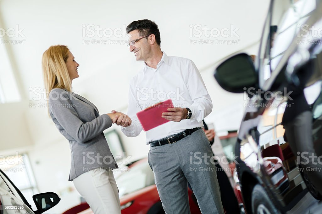 Salesperson showing vehicle to potential customer royaltyfri bildbanksbilder