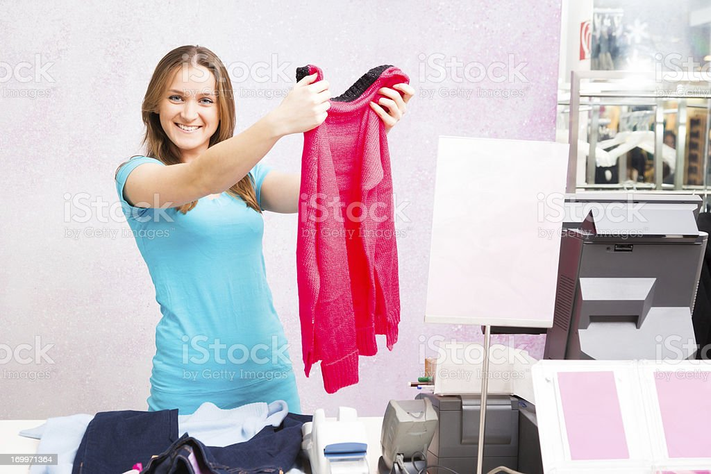 salesperson standing at cash register in fashion store royalty-free stock photo
