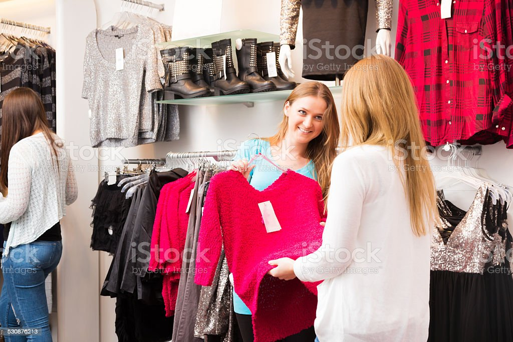 Salesperson Talking To Customers In Fashion Store Stock Photo & More ...