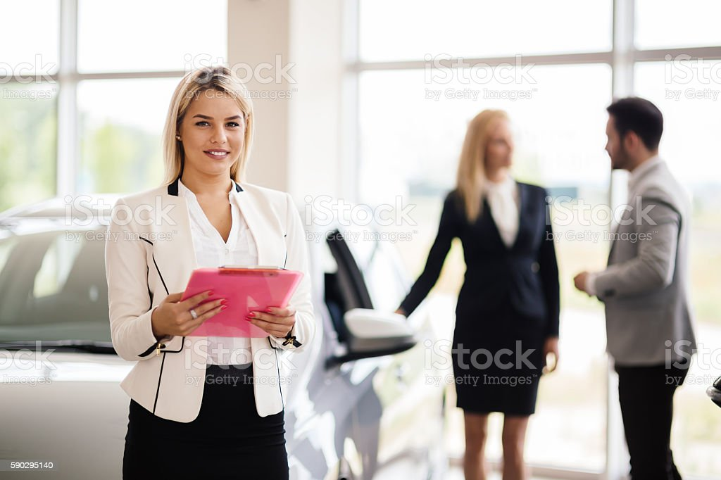 Salesperson working at car dealership royaltyfri bildbanksbilder