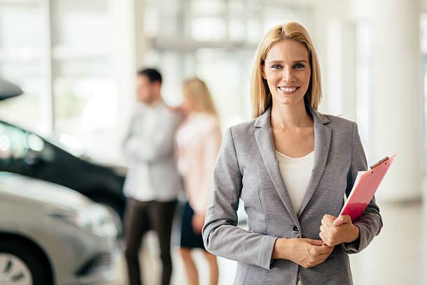 salesperson working at car dealership - verkoopster stockfoto's en -beelden