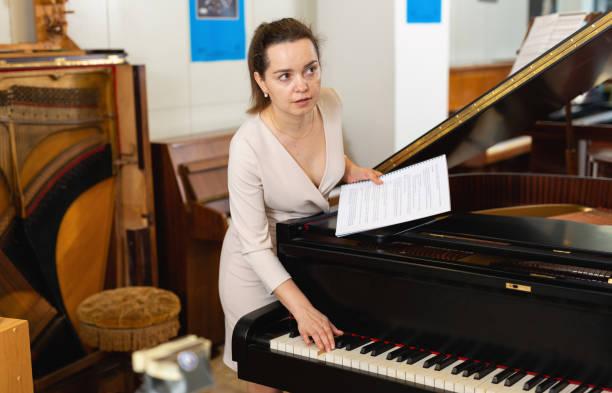 verkäuferin assistentin im klaviermusikgeschäft - klavier verkaufen stock-fotos und bilder