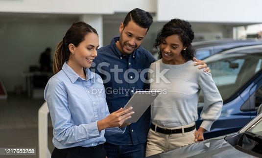 Portrait of a saleswoman at a car dealership talking to a happy couple and showing them info on a tablet computer - business concepts