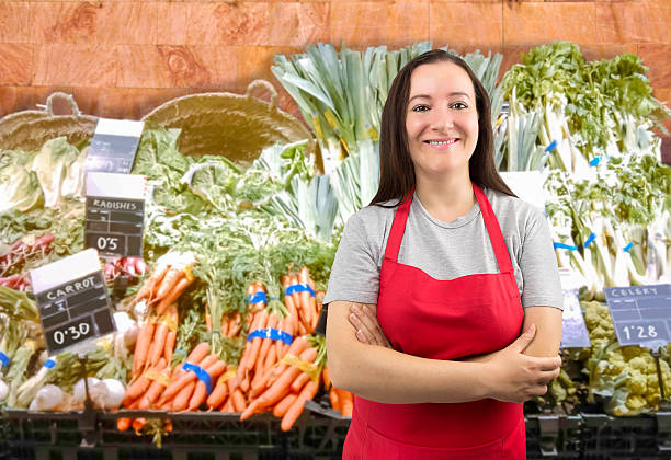 saleswoman at the greengrocer portrait of saleswoman at the vegetables store with crossing arms grocer stock pictures, royalty-free photos & images