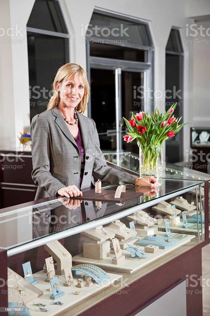 Saleswoman behind counter in jewelry store stock photo