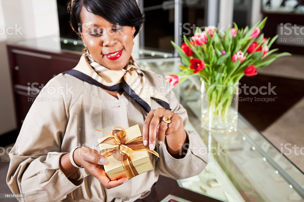 Saleswoman behind counter in jewelry store with gift box stock photo