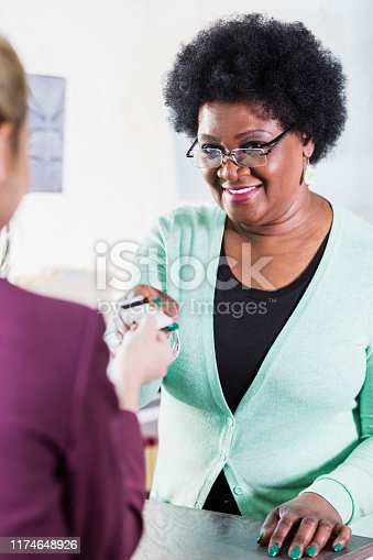 istock Saleswoman giving back credit card to customer 1174648926