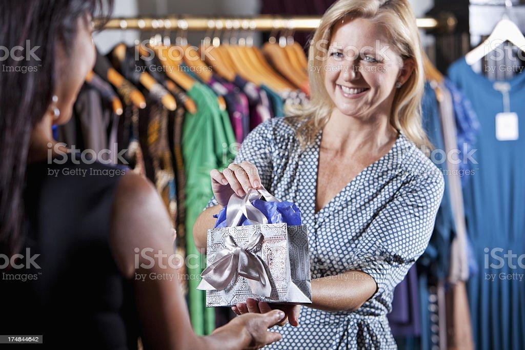 Saleswoman handing customer a gift bag royalty-free stock photo