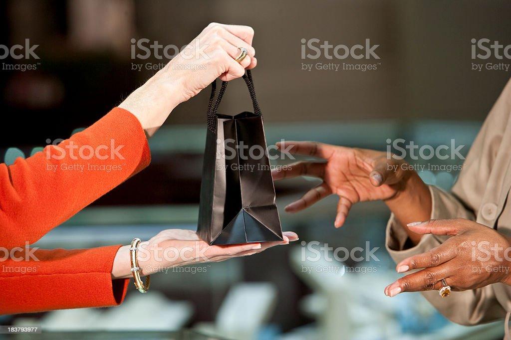 Saleswoman handing shopping bag to customer stock photo