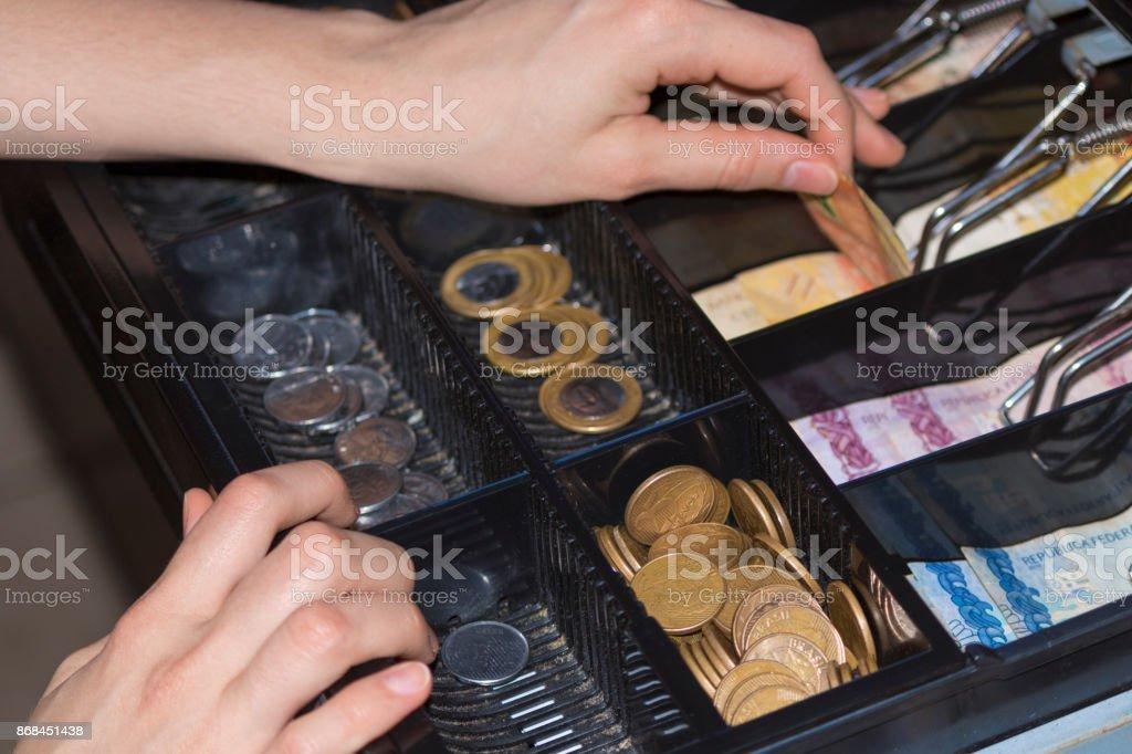 Manos de la vendedora en la caja registradora con dinero brasileño billetes y monedas dentro de la caja registradora electrónica - foto de stock