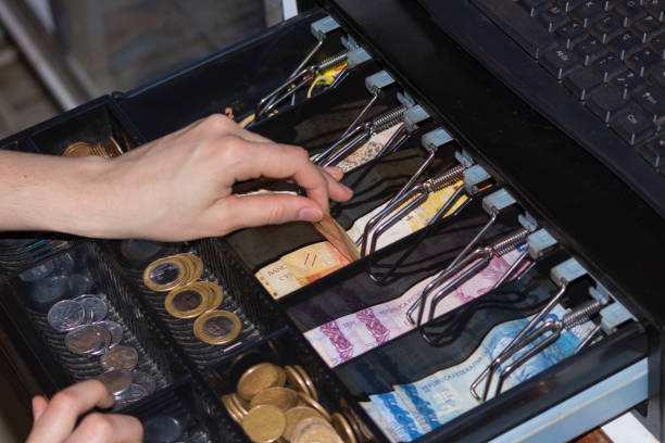 verkäuferin hände an kasse mit brasilianischen geld banknoten und münzen in die elektronische registrierkasse - klavier verkaufen stock-fotos und bilder
