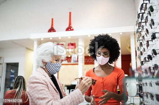 Saleswoman helping costumer in an optical store, both wearing mask