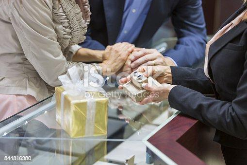 478253473istockphoto Saleswoman helping couple in jewelry store 844816380