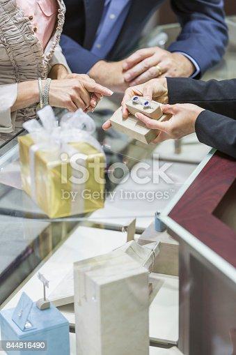 478253473istockphoto Saleswoman helping couple in jewelry store 844816490