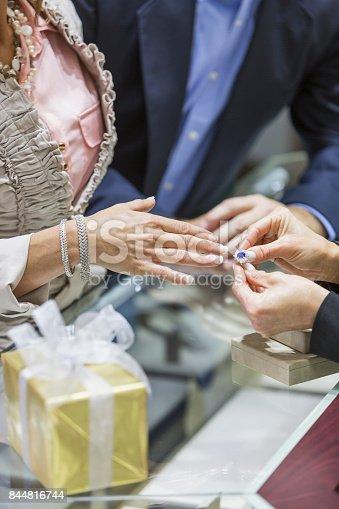 478253473istockphoto Saleswoman helping couple in jewelry store 844816744
