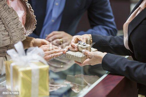 478253473istockphoto Saleswoman helping couple in jewelry store 856747066