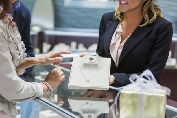 Saleswoman helping couple in jewelry store Cropped view of a saleswoman in a jewelry store helping a mature couple, showing the female customer a ring and necklace from the display case. jeweller stock pictures, royalty-free photos & images