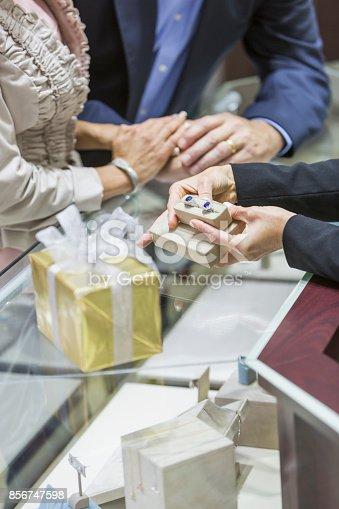 478253473istockphoto Saleswoman helping couple in jewelry store 856747598