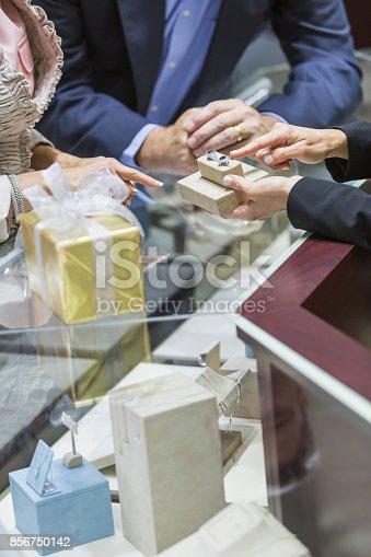 478253473istockphoto Saleswoman helping couple in jewelry store 856750142