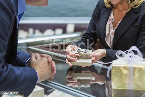 478253473istockphoto Saleswoman helping man shop for jewelry 844816388