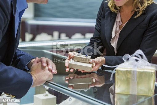 478253473istockphoto Saleswoman helping man shop for jewelry 856747356