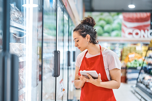 Saleswoman working in supermarket. Female owner looking at refrigerator while holding digital tablet at store. She is wearing apron.