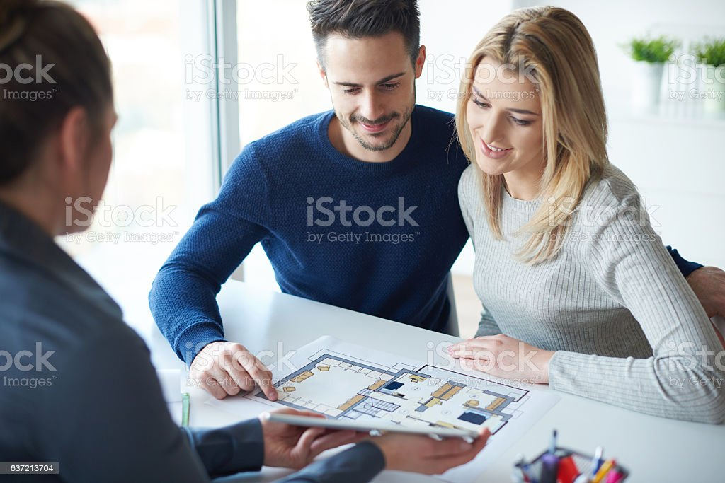 Saleswoman showing paperwork to couple stock photo