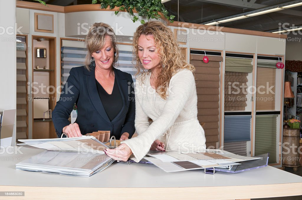 Saleswoman showing window shades to interested customer royalty-free stock photo
