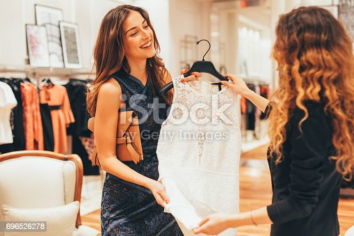 Saleswoman suggesting dress to a customer at a clothing store.