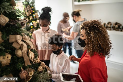 Saleswoman supporting a customer in a christmas ornament store
