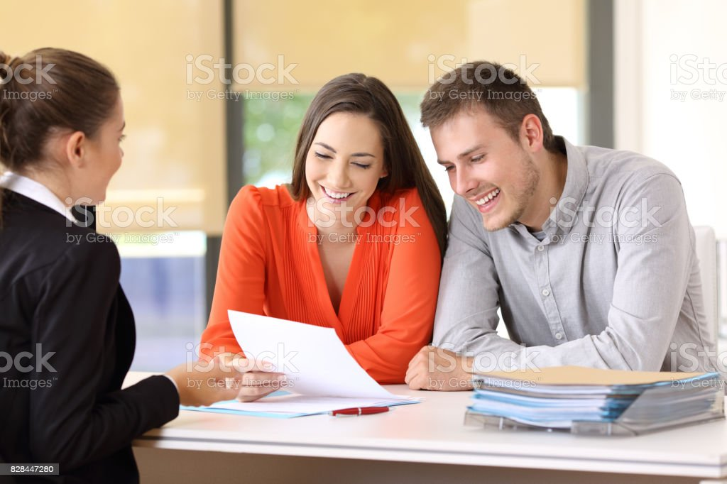 Saleswoman talking with customers at office stock photo