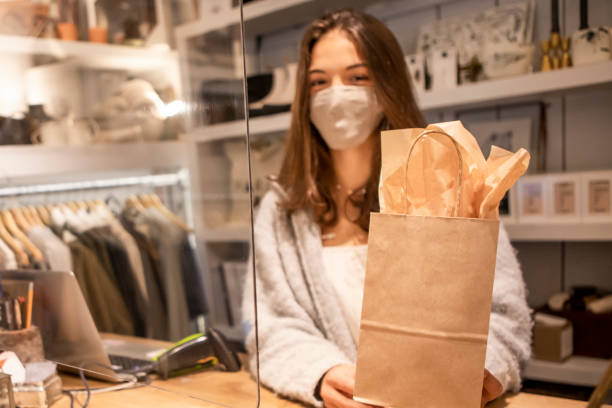 Saleswoman wearing protective face mask in retail shop.