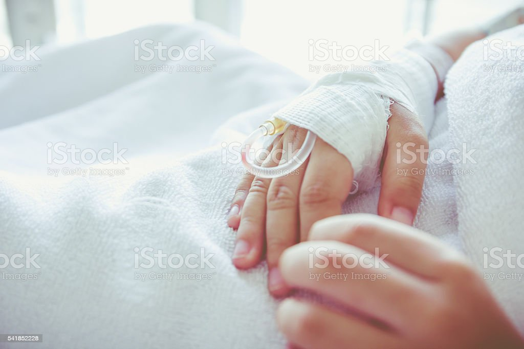 Saline intravenous (iv) drip in a child's patient hand. Vintage stock photo