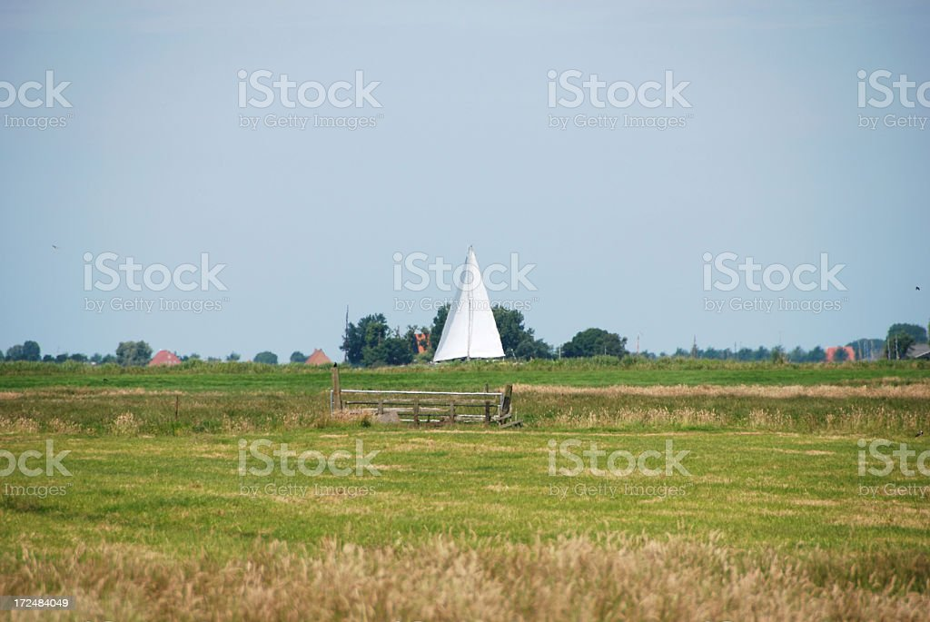 Saling boat is passing true the pasture royalty-free stock photo