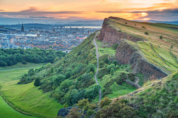 Salisbury Crags in Holyrood Park and downtown Edinburgh Scotland Stock photograph of Salisbury Crags in Holyrood Park and downtown Edinburgh Scotland UK during sunset edinburgh scotland stock pictures, royalty-free photos & images
