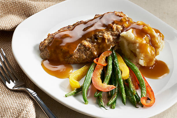 Salisbury Steak with Mashed Potatoes and Gravy Salisbury Steak with Mashed Potatoes and Gravy served with stir fry green beans and peppers. burwellphotography stock pictures, royalty-free photos & images