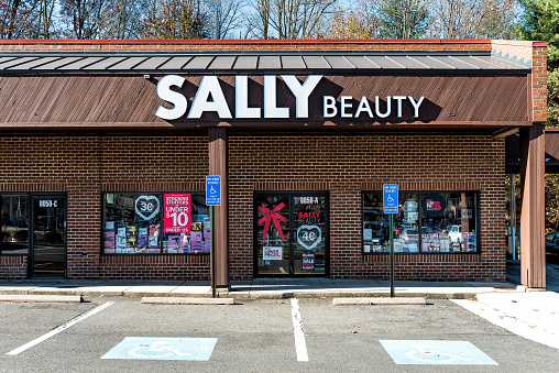 Burke, USA - November 24, 2017: Sally Beauty Supply store in plaza shopping center strip mall sign in Virginia with parking lot, shops