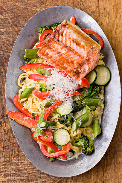 Salmon And Pasta Primavera Platter An overhead close up shot of a old pewter platter with some pasta primavera and a piece of grilled king Salmon filet. primavera stock pictures, royalty-free photos & images