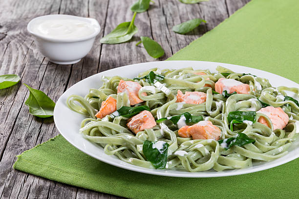 lachs und spinat-fettuccine nudeln auf weiß schüssel - spaghetti mit lachs stock-fotos und bilder