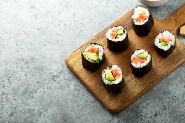 rouleaux de sushi d'avocat de saumon - sushi photos et images de collection