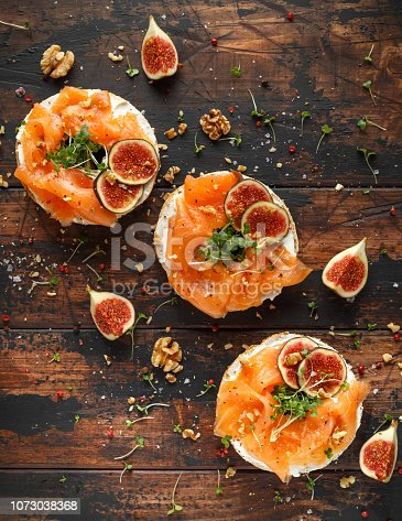 istock Salmon Bagel Sandwich with figs, cress salad, walnuts, cream cheese and grain on rustic wooden background. healthy breakfast 1073038368