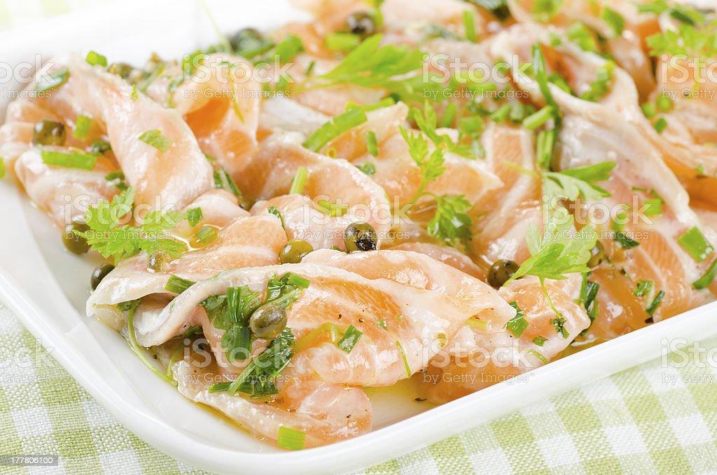 Salmon carpaccio - fresh fish slices in marinade royalty-free stock photo
