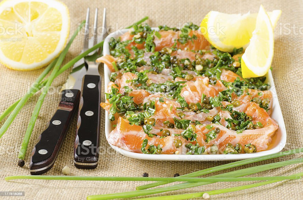 Salmon carpaccio - fresh fish slices in marinade stock photo