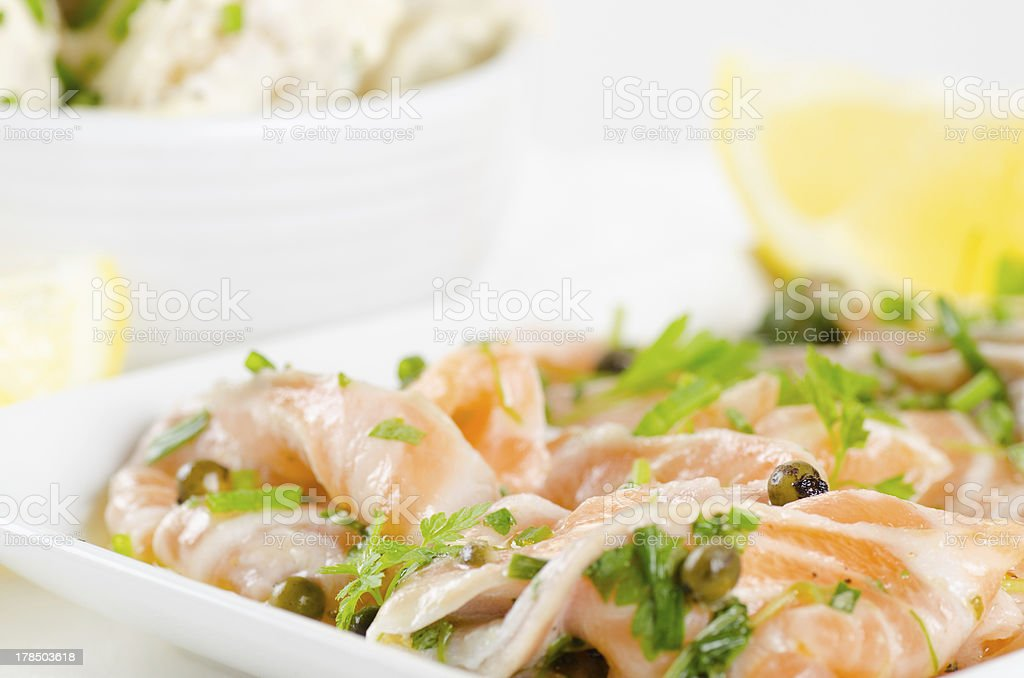 Salmon carpaccio with potato salad and lemon on white stock photo