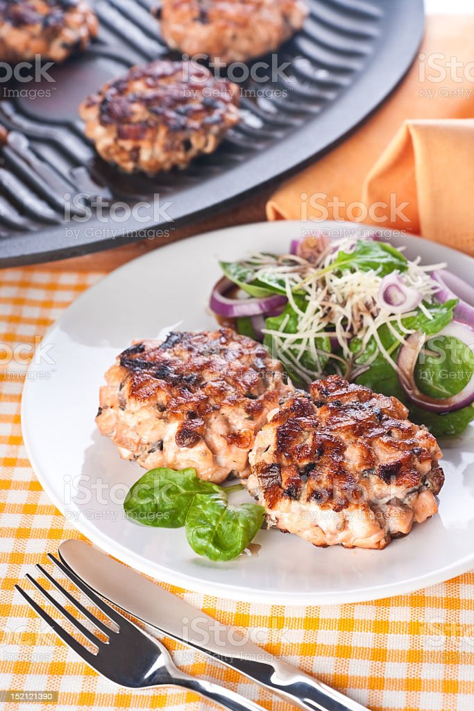 Salmon cutlet with a salad of spinach and onion royalty-free stock photo
