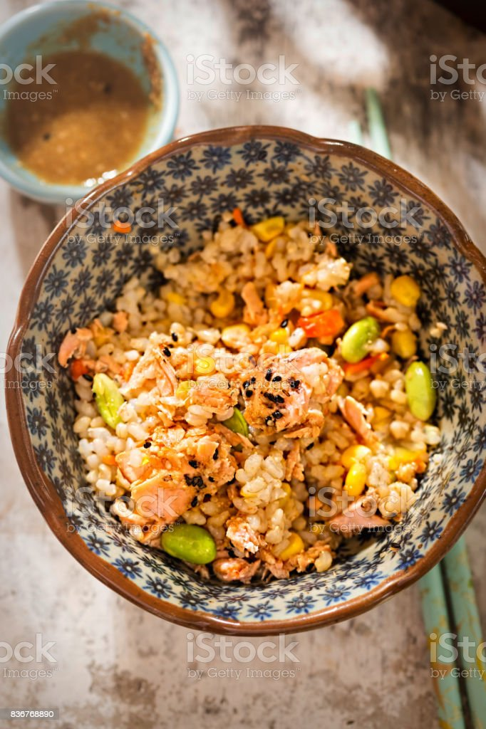 Salmon, edamame, brown rice meal pot with Japanese sesame sauce stock photo