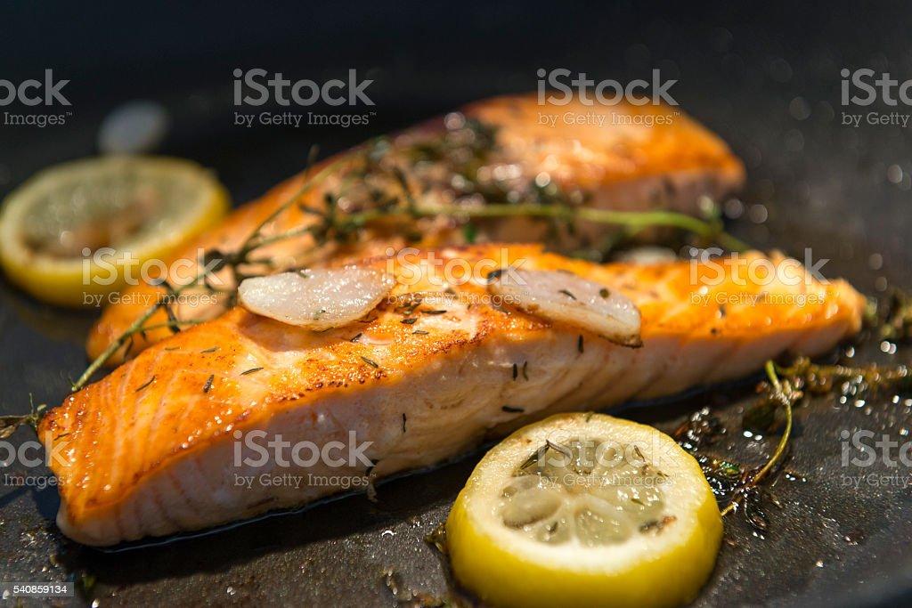 salmon filet in a frying pan stock photo