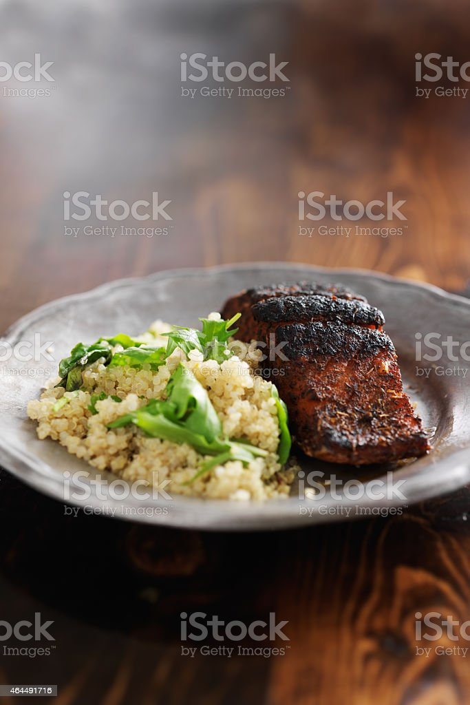 salmon filet with quinoa and arugala on wood table stock photo