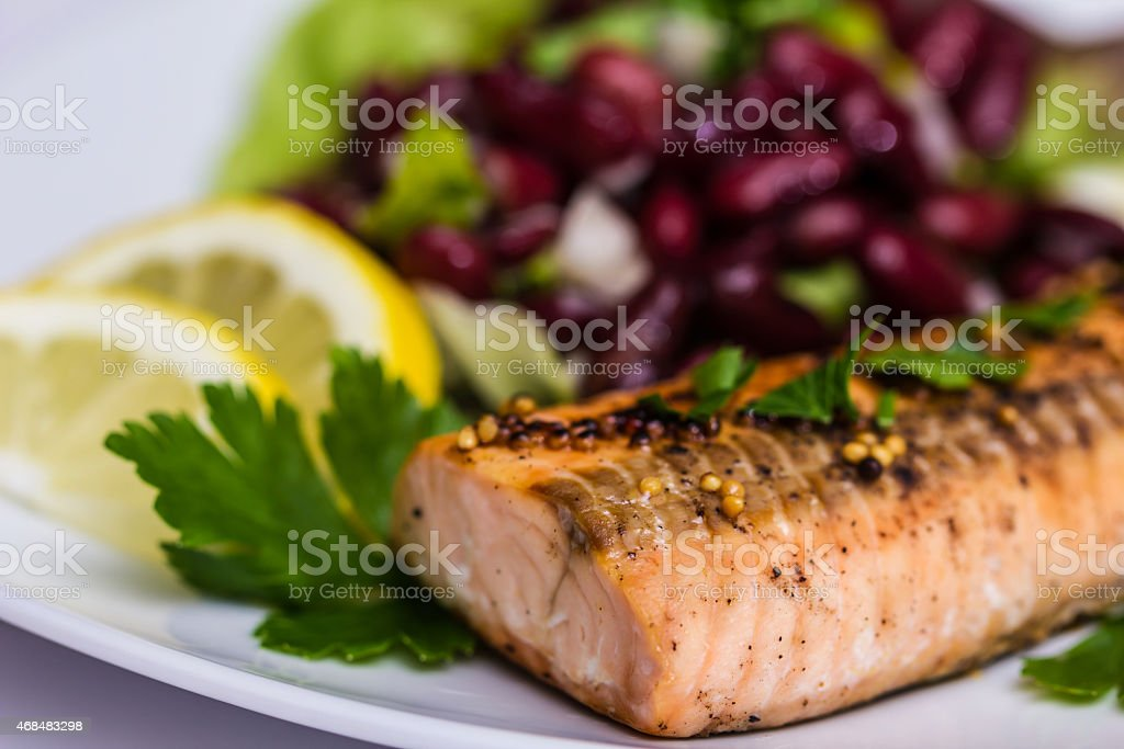 Salmon fillet grilled with bean salad, lemon and parsley stock photo