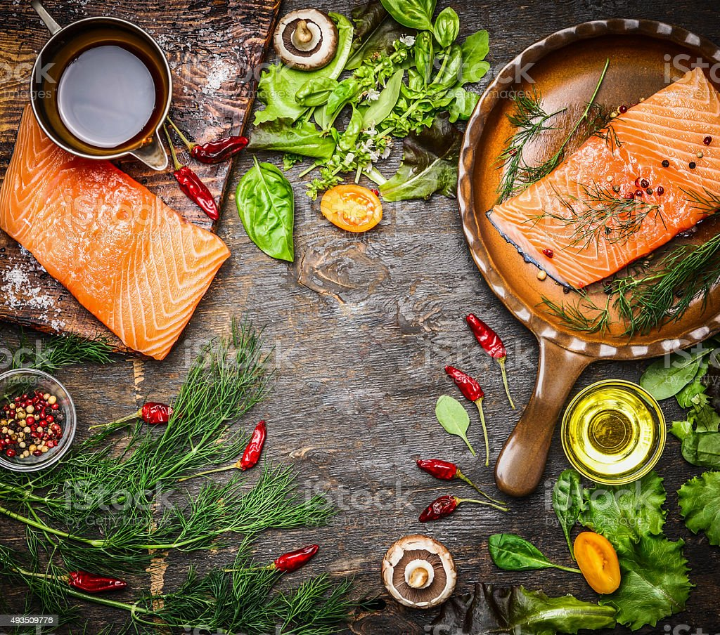 Salmon fillet on rustic table with fresh ingredients for cooking stock photo